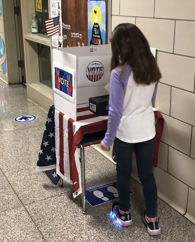 Girl casts her ballot in school.