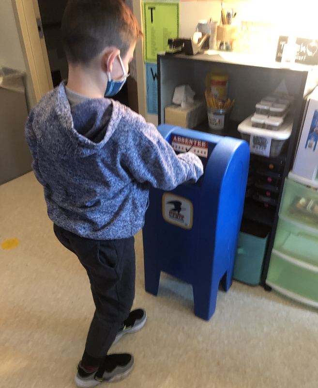 Boy drops his ballot in makeshift mail box.